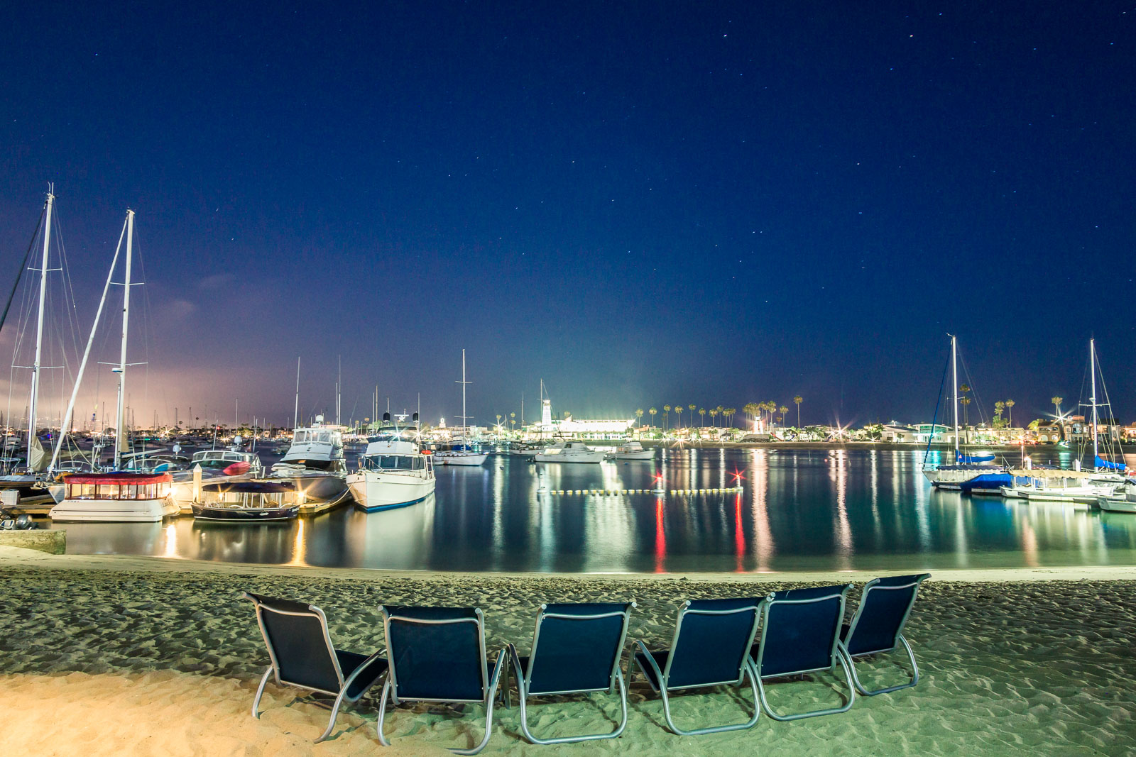 Lido Island beach With a view of the harborIlluminated at night with palm trees and lounge chairs