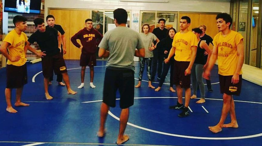 Head Youth Outreach Coach Jerry Cepeda on the mats with his students at the Eric Solorio Academy