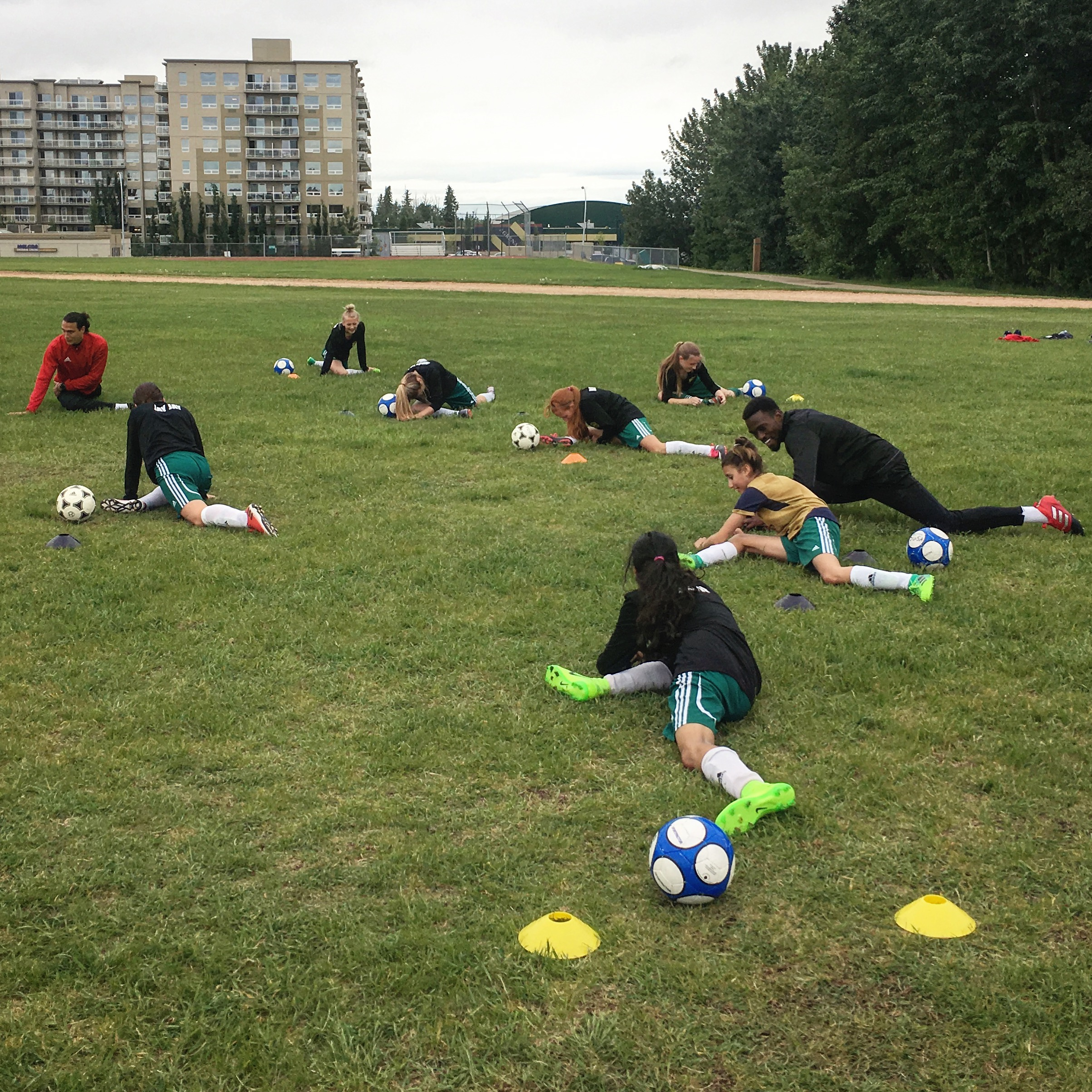 Spruce Grove U12 Girls doing the pigeon pose, a great mobility exercise.
