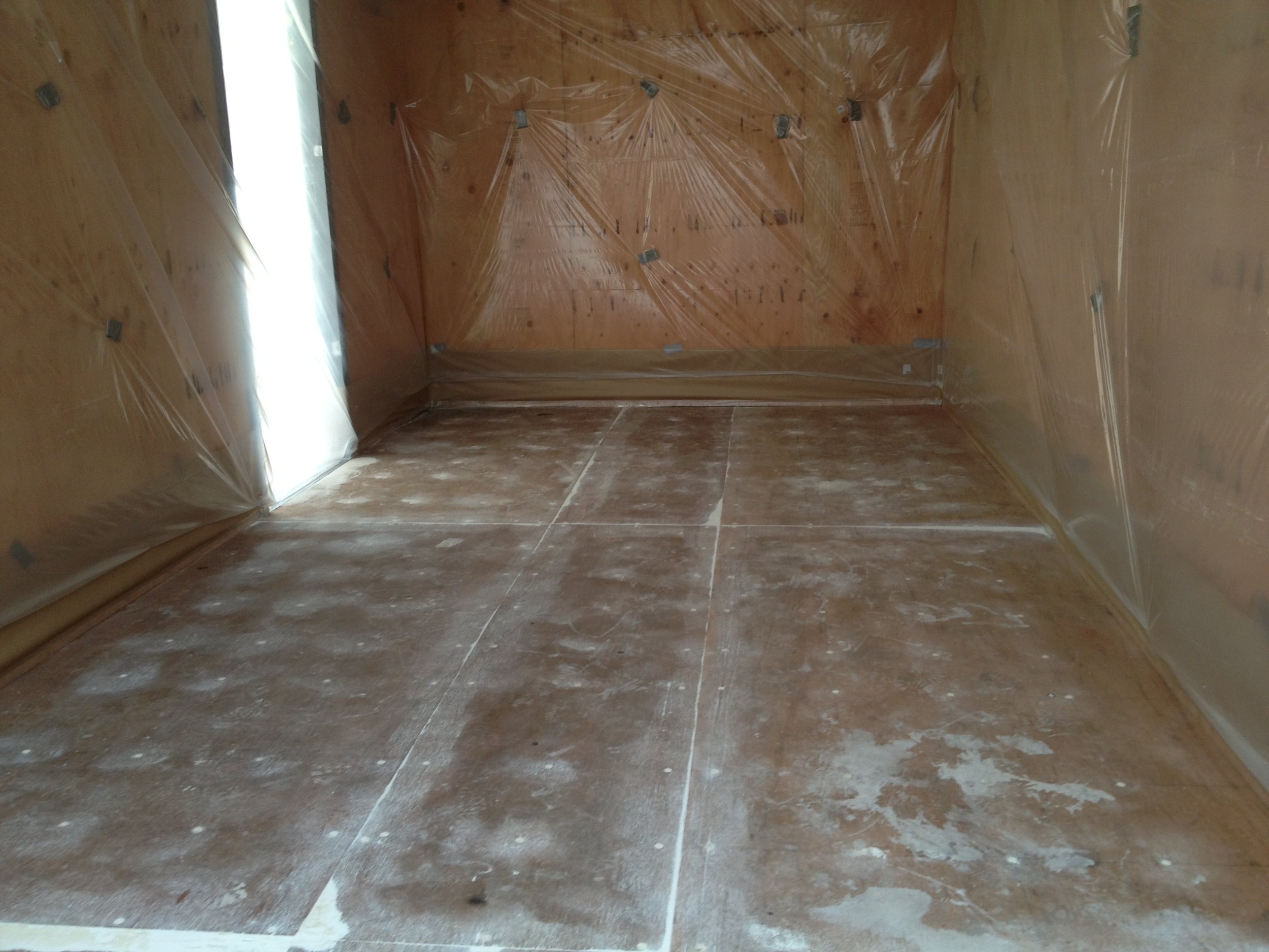 Before - An unprotected connex floor prepped for a protective polyshield layer.