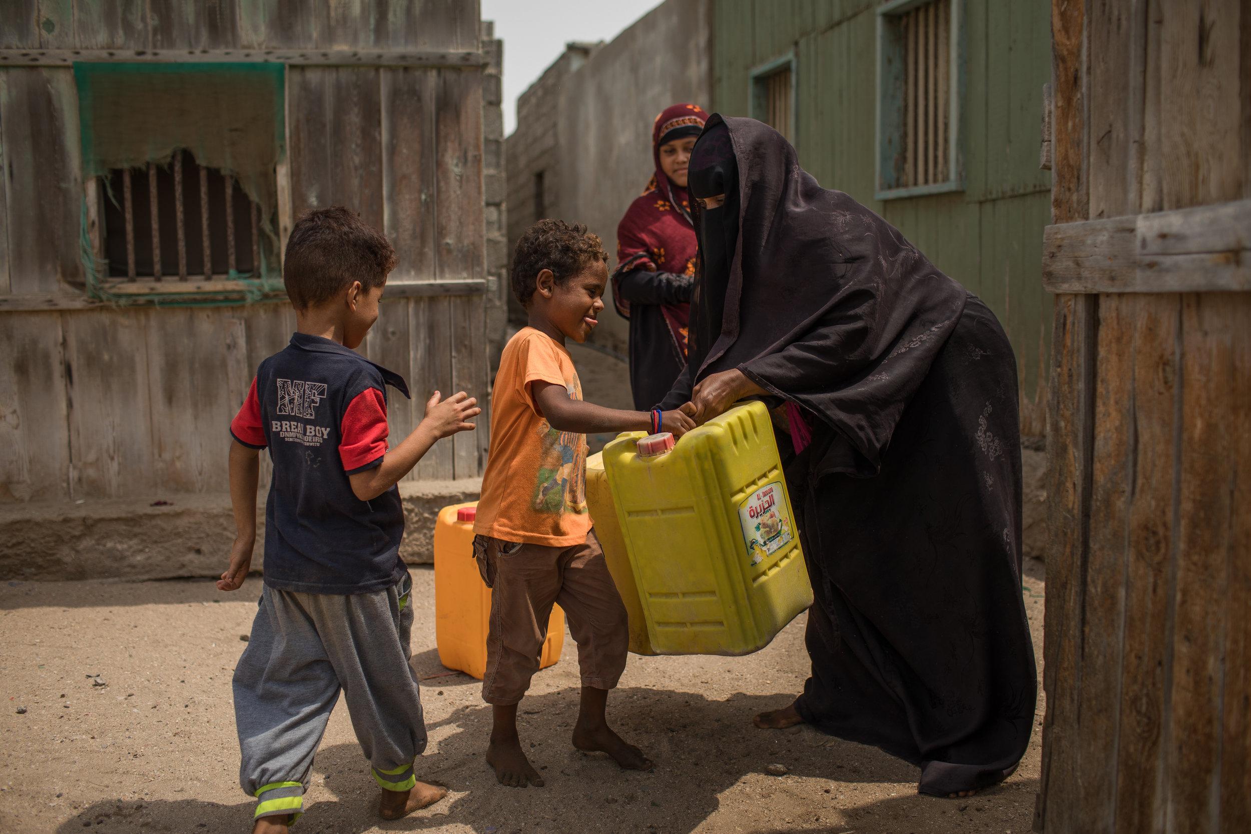 Kinder erhalten Wasser in ihrem Dorf in Jemen. Foto: Kellie Ryan / IRC