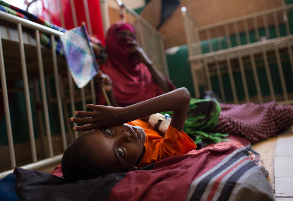 Ein kleiner Junge liegt auf einem Kinderbett im Krankenhaus von Mogadischu, wo er wegen Unterernährung behandelt wird. Quelle: Will Swanson/IRC