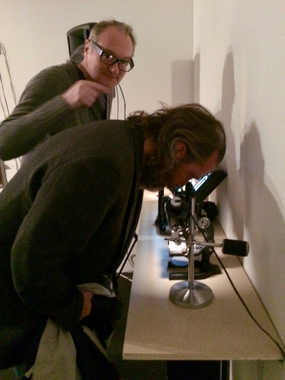 Chris Benker and Denis get a stereo-microscopic view of a working wrist watch at Lary 7's art installation. Photo by Shari Berman