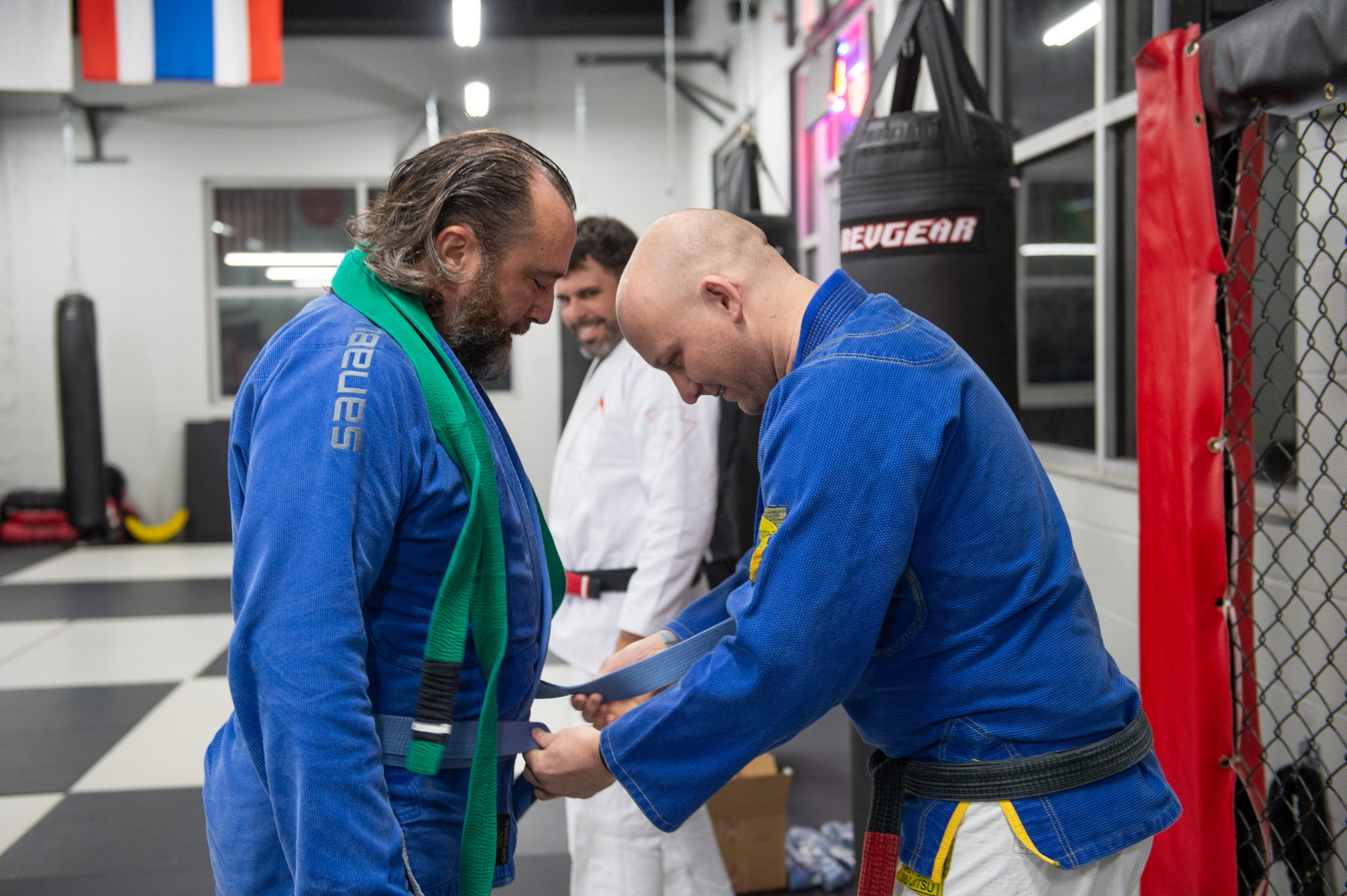 Photo Credit;  Joed Viera . Denis receives a blue belt in Jiu Jitsu from professors Josh Ketry (background) and Larry Backlas at  Buffalo United Martial Arts .