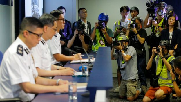Journalists wearing helmets and reflective vests in a press release of the Hong Kong Police Force to silently protest against the police brutality towards the media    Photo Source: BBC