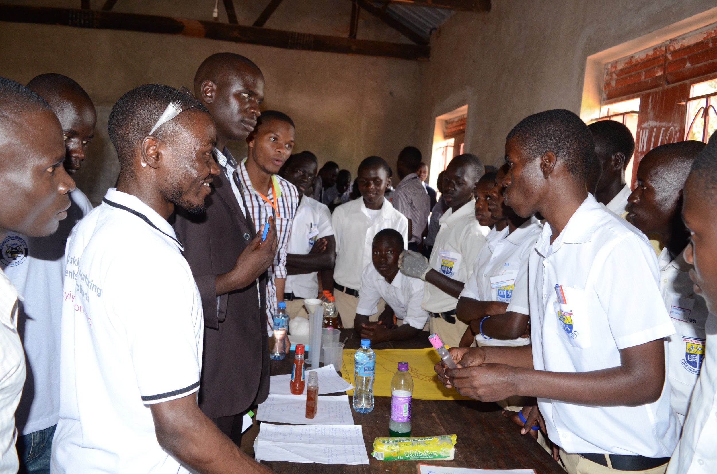 Students from Lira town College explain to Judges the science behind their locally made hand sanitizer.JPG