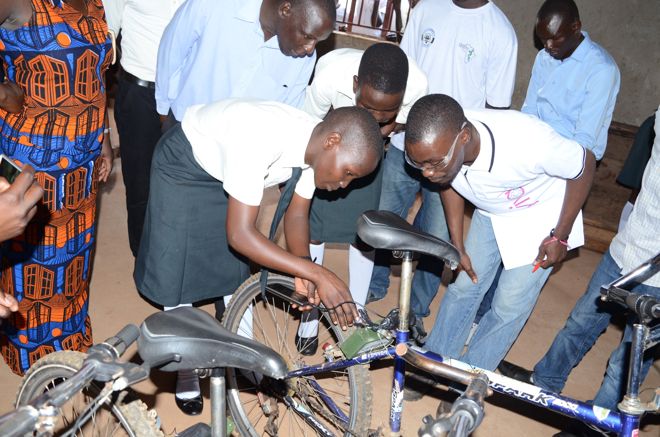 A student engineer from Leo Atubo College shows a judge how their bicycle powered charger works (3).JPG