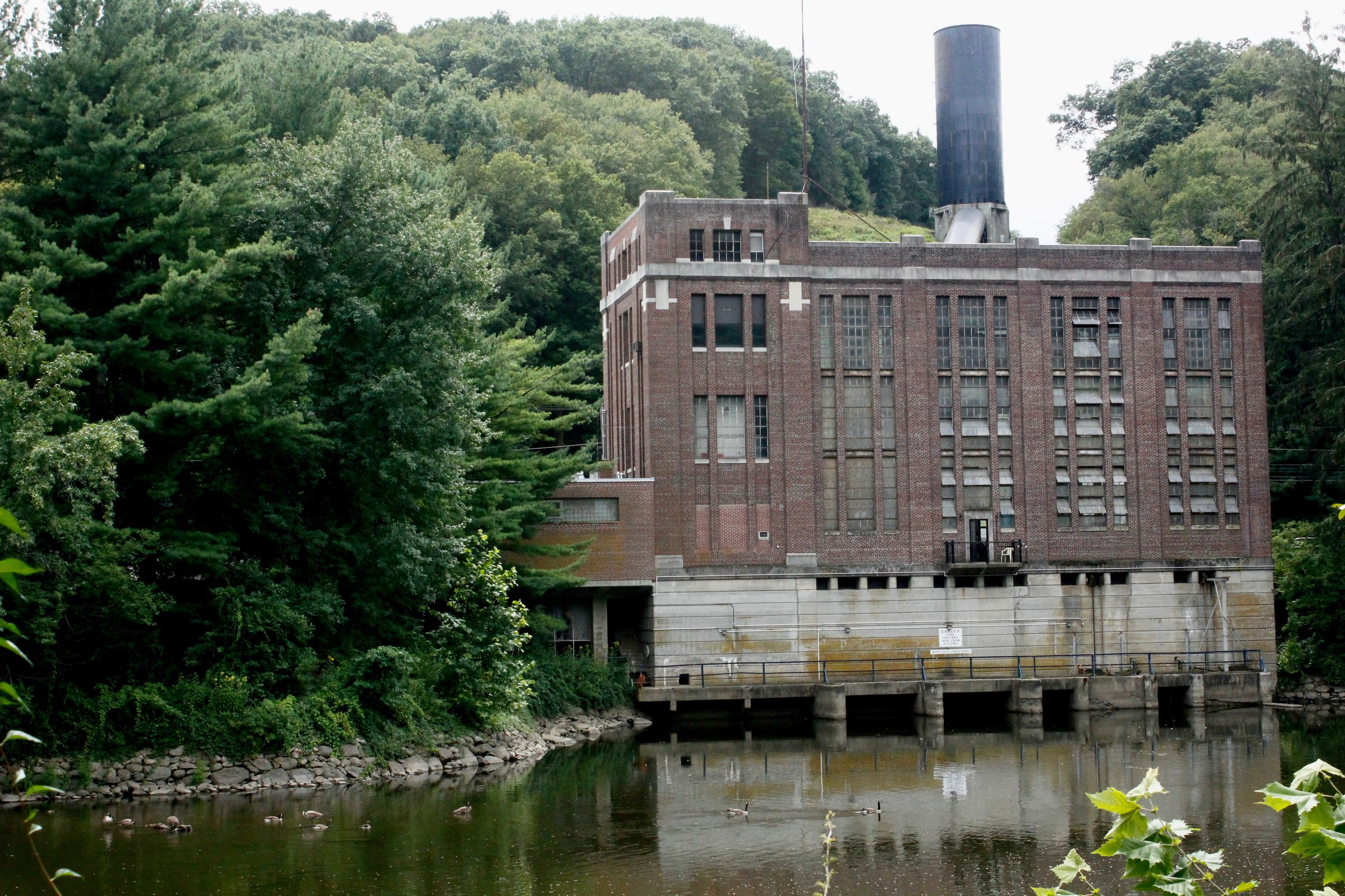 This is the back side of the power plant, and the Housatonic River below.  Once the water flows through the pipe, into the power plant, where its momentum is used to spin turbines that create electricity, the  now slow moving water is discharged into the river. The water gets pumped back up to the lake when there is low power demand and electricity is cheap, typically at night.