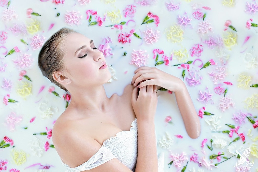 HNHS senior, Saige laying in a milk bath with floral elements for a portrait with Feather & Key.