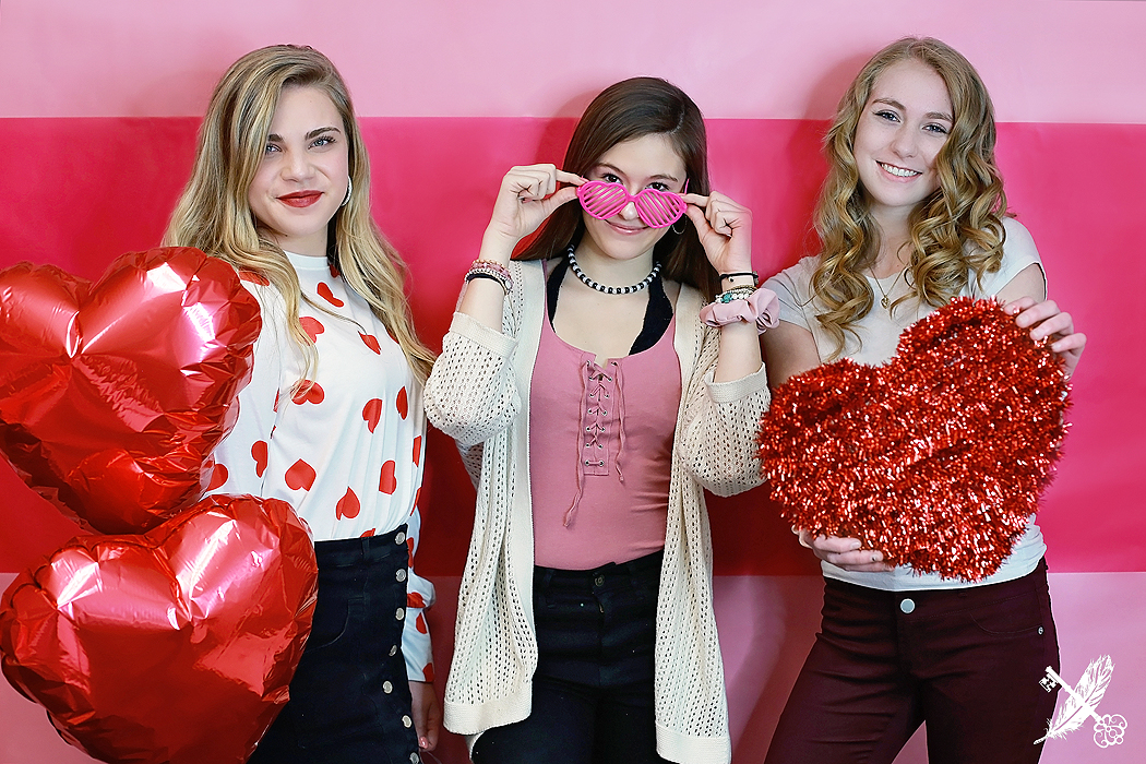 Three HNHS seniors with heart props for galentines day photo shoot at feather and key studio in huntington.