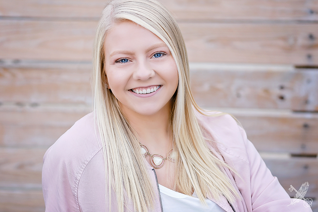 HNHS senior girl smiles in front of wooden pallet wall in downtown Huntington indiana with feather and key photography watermark in corner.