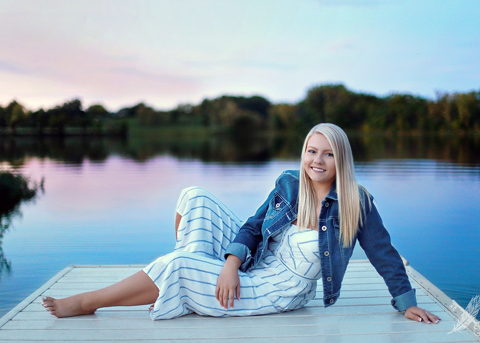 HNHS senior smiling and laying on a dock at lake at sunset in Huntington indiana with feather and key photography watermark in corner.