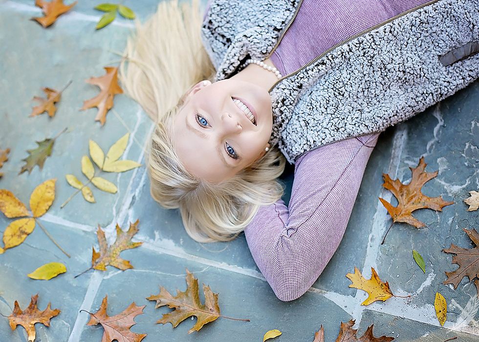 High school girl laying in fall leaves for senior photos with feather and key photography.