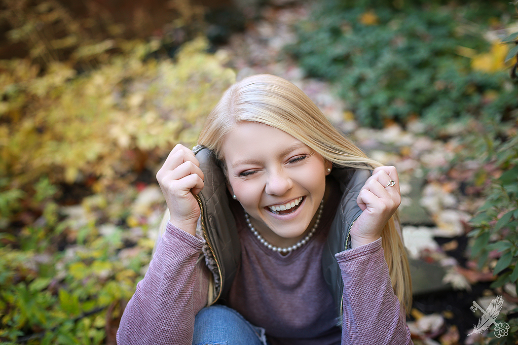 Huntington North High School senior laughs surrounded by fall leaves for her pictures with feather and key photography.