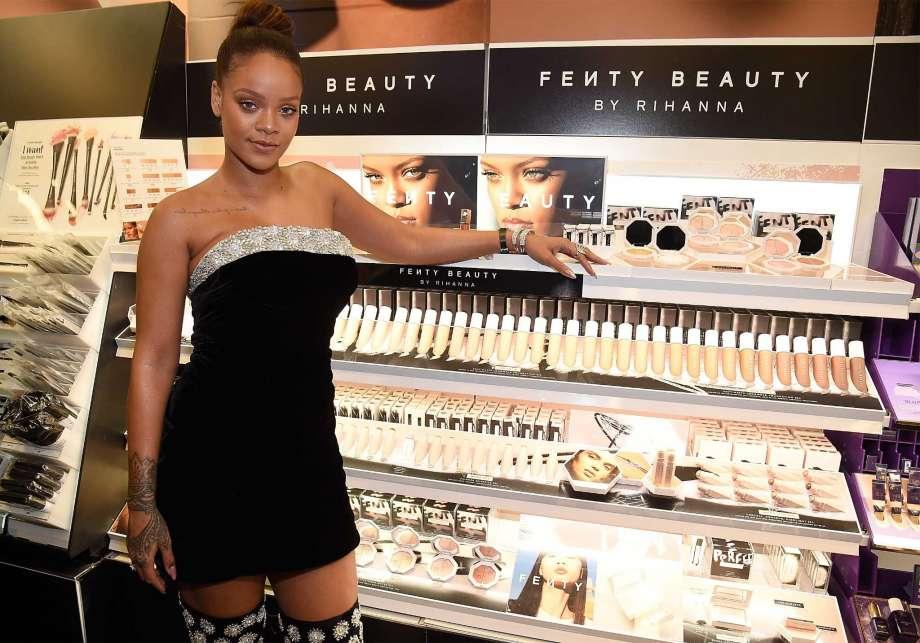 Rihanna next to a  Fenty Beauty display, photo via  Kevin Mazur