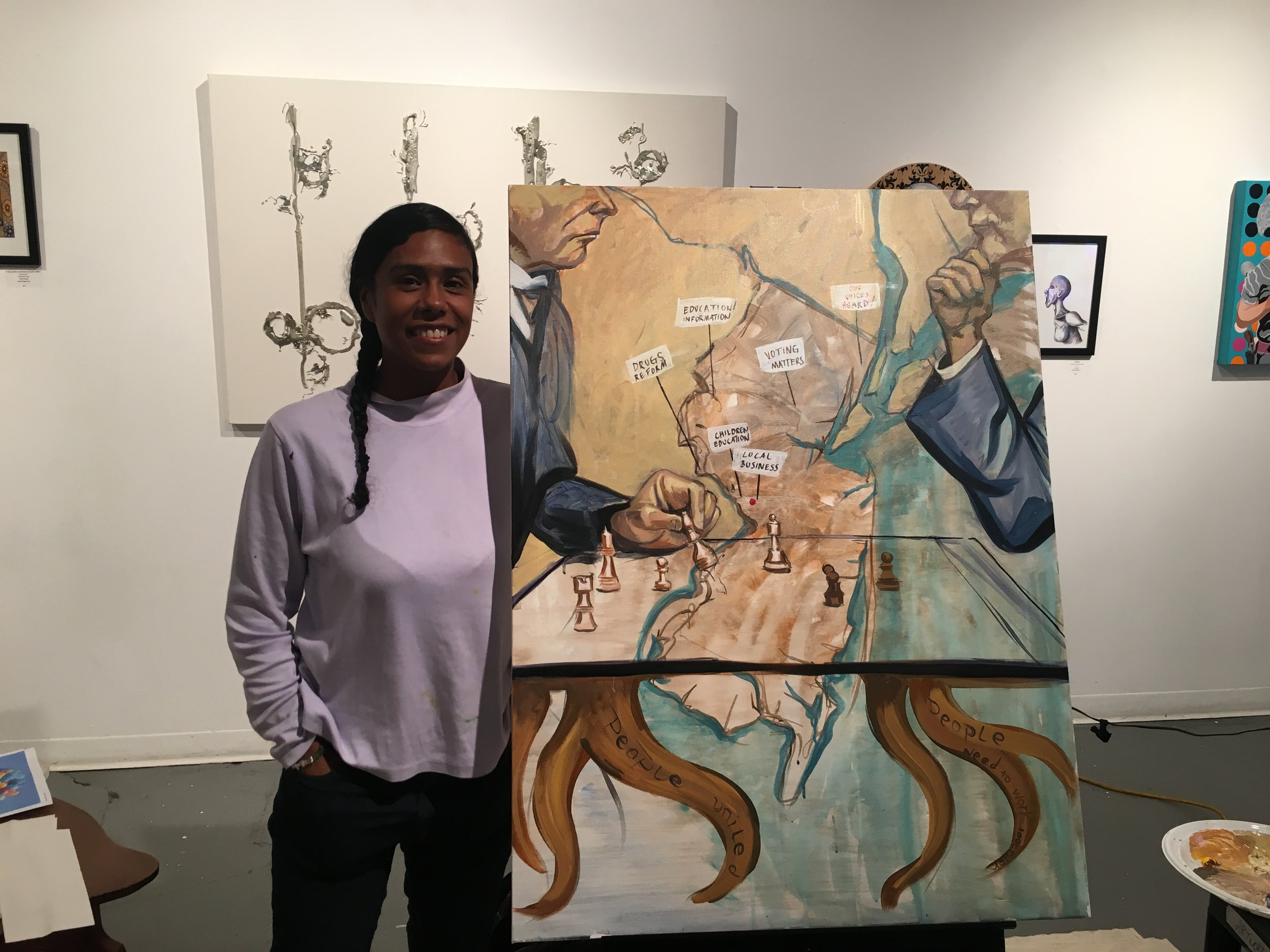 Marthalicia Matarrita poses with the painting she created during Artworks' Political Potluck.