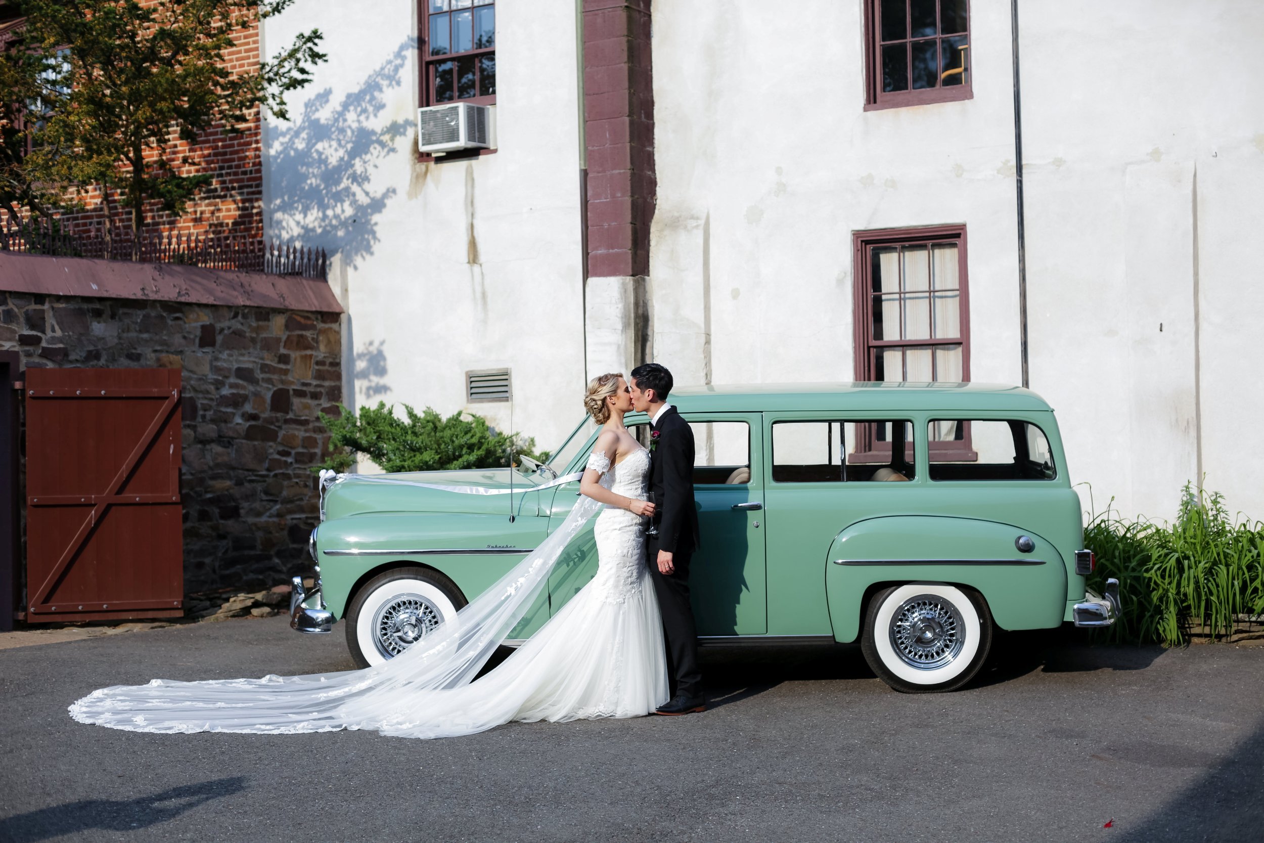 Bride and groom in front of antique car