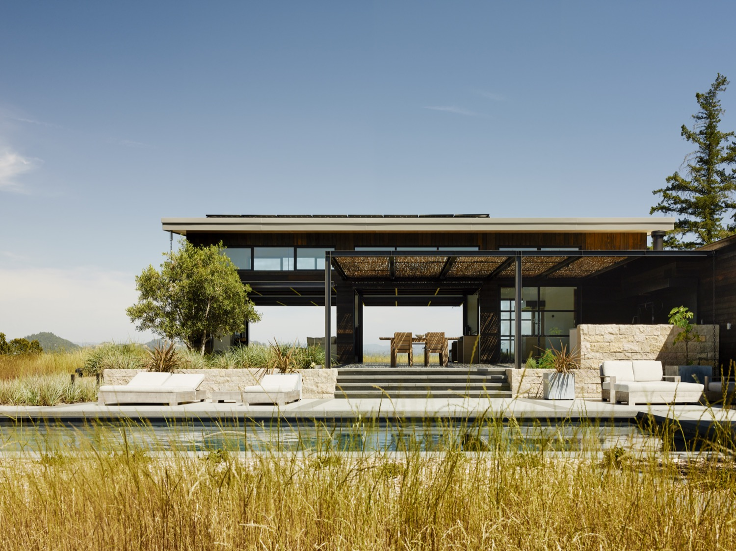 The pavilion-like living room opens up to the outdoor dining and pool