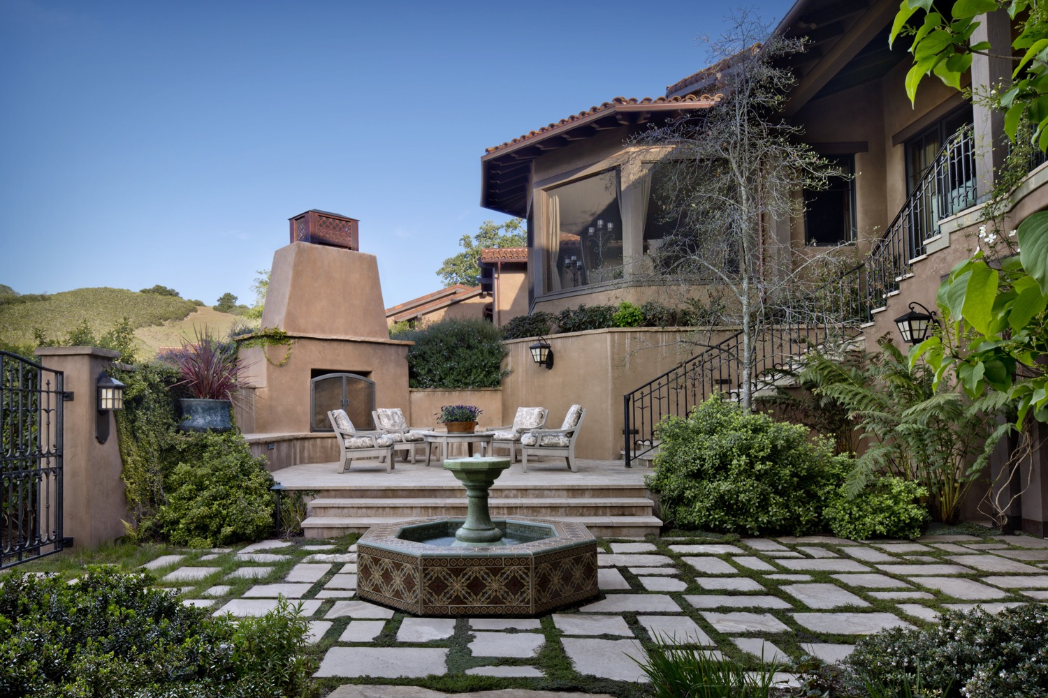 On the opposite side of the home from the pool, a sunken courtyard provides continual shade and a fireplace.