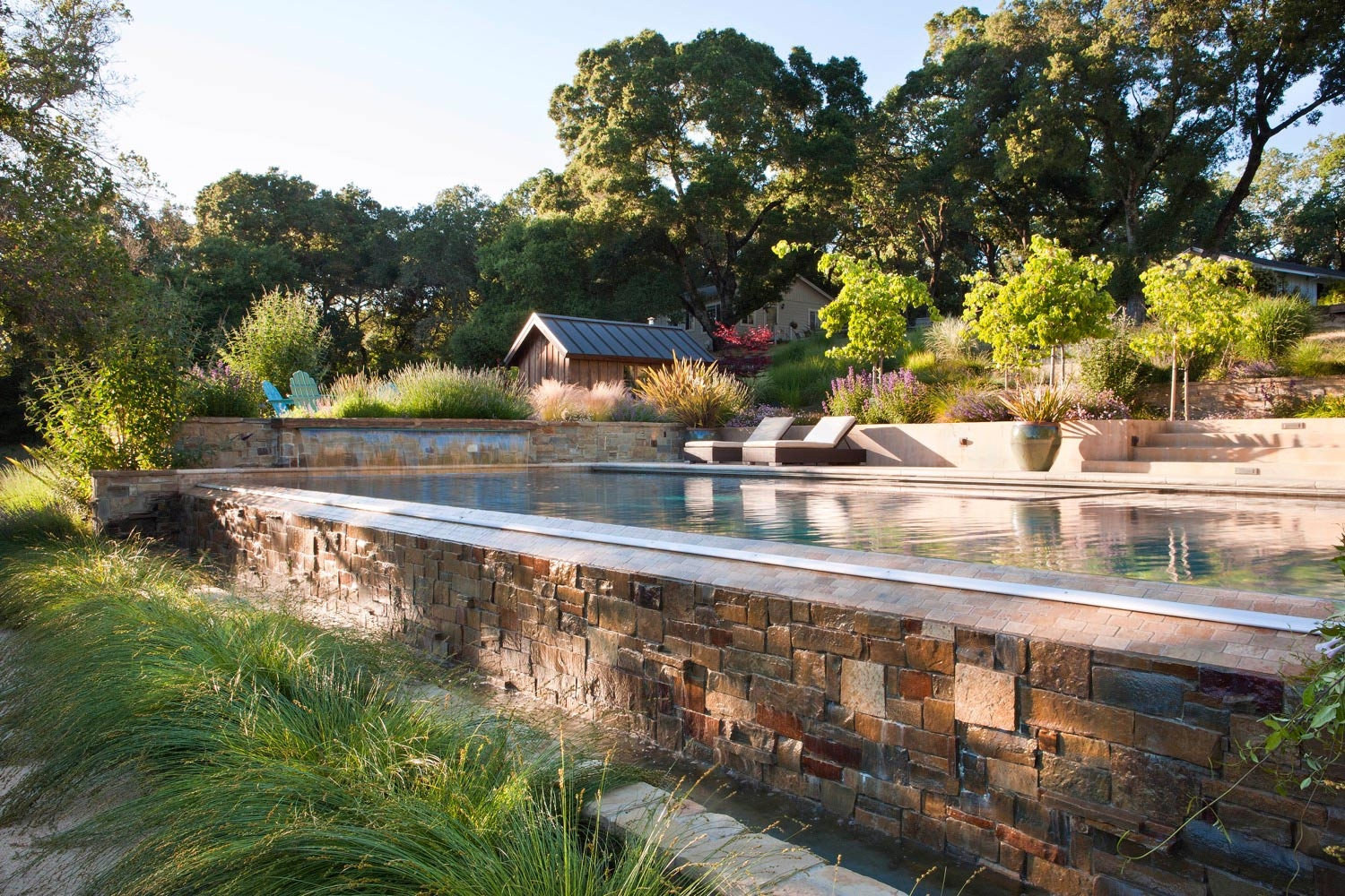 The pool has a vanishing edge along its long side, where the water falls over a stone surface like a fountain.