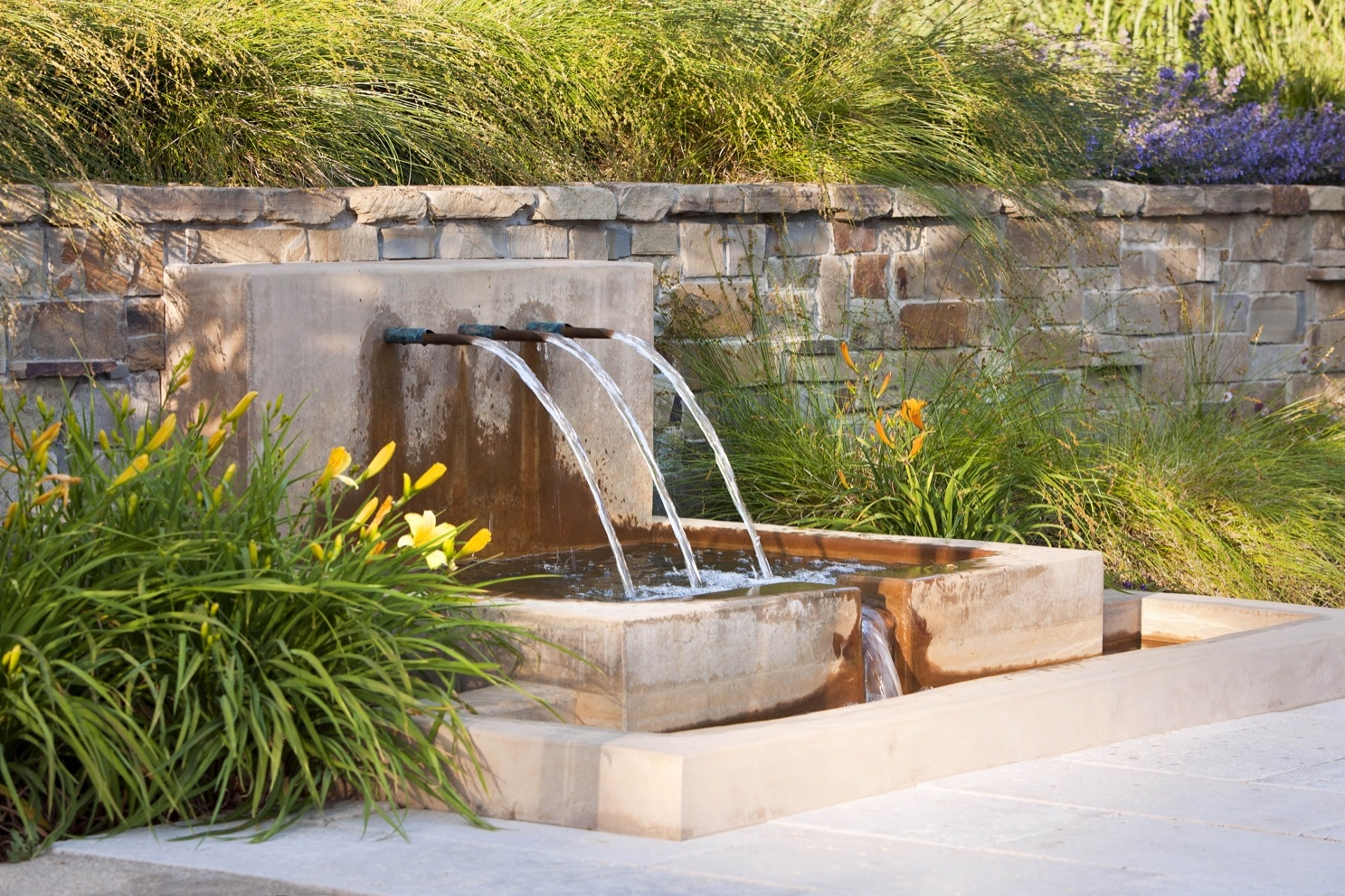 A second fountain provides the soft sound of falling water near a gathering area.