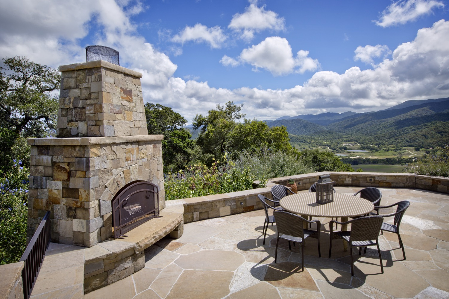 The expansive outdoor dining terrace is anchored by a large fireplace, perfect for large family gatherings.