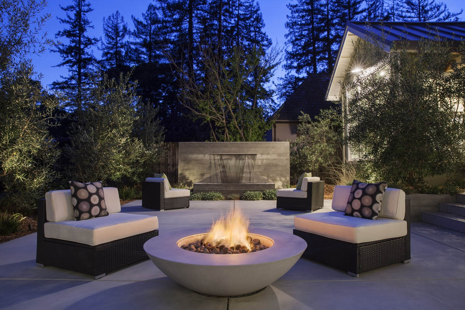 The firepit provides warmth and the fountain provides the calming sound of water. The firepit is finished in a very smooth concrete, while the fountain provides contrast in board-formed concrete.