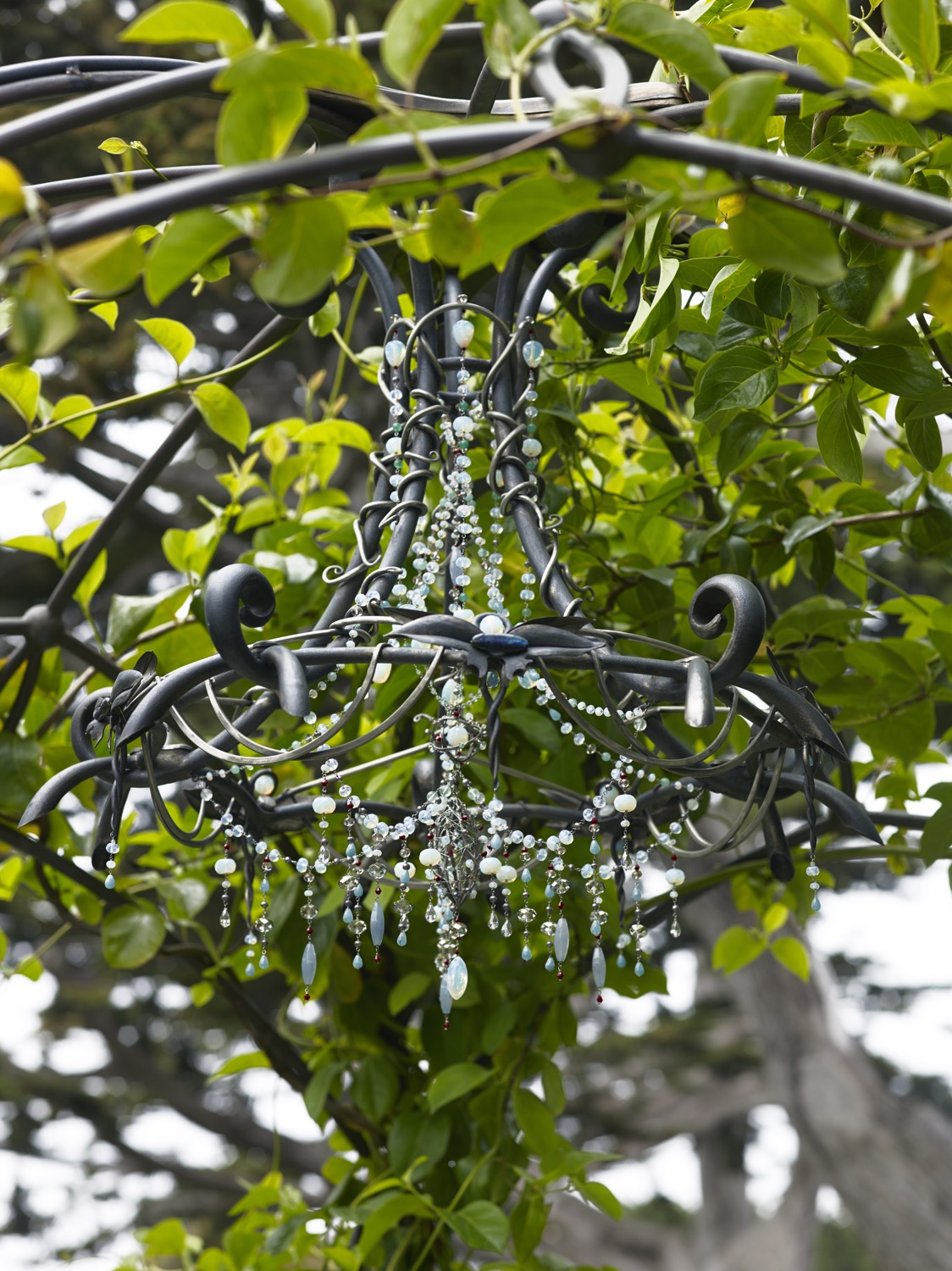 A custom designed metal chandelier with blue beadwork hangs from a metal arbor.
