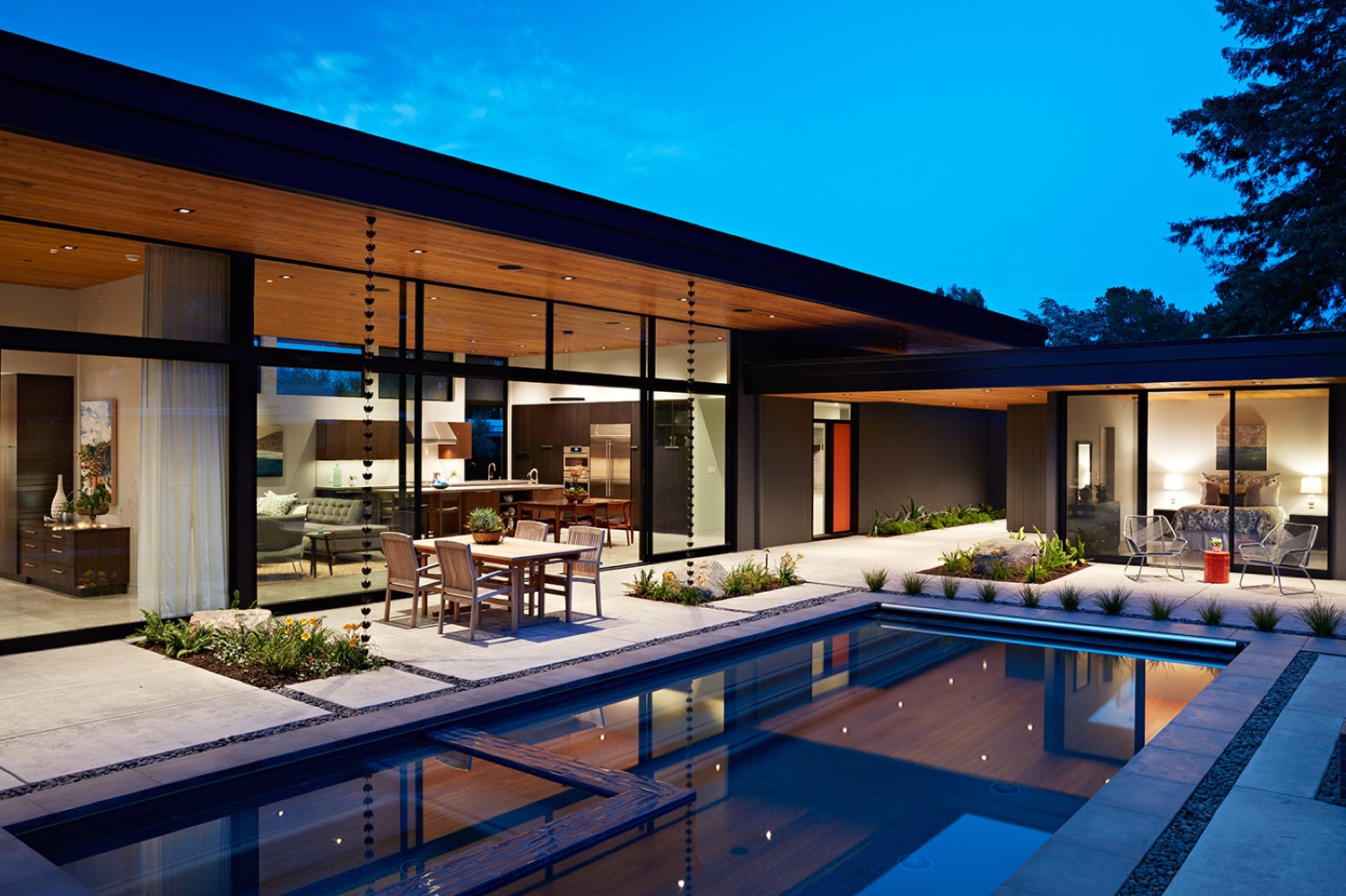 With the architectural and landscape lighting turned on at night, the glass wall seems to disappear, enhancing the connection of indoor and outdoor.