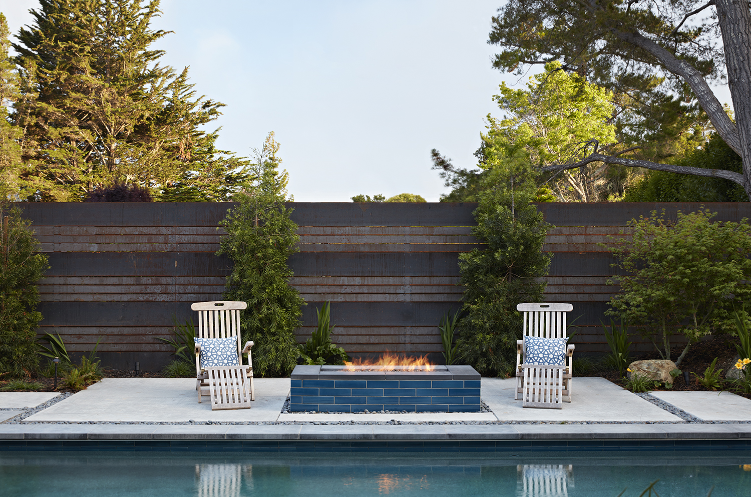 The blue-tiled is in front of a weathered zinc fence, for fire safety and textural interest.