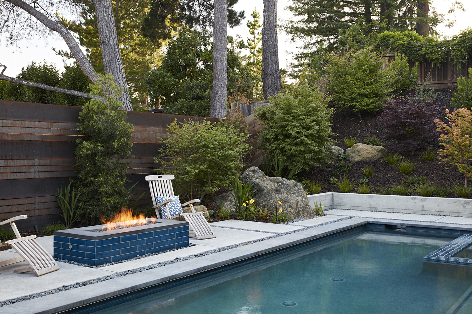 A metal fence sits behind the blue tiled firepit for fire safety.