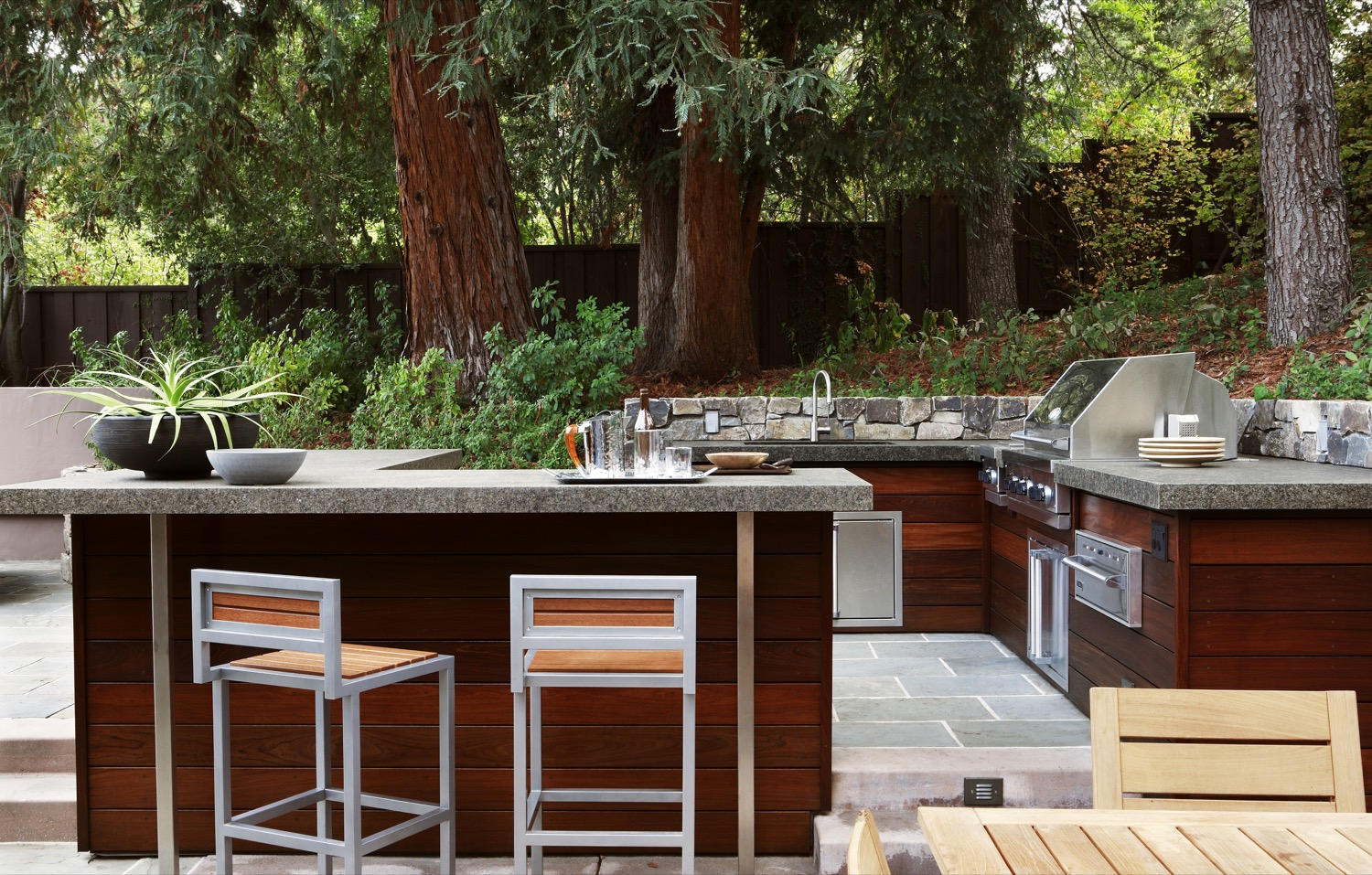 The large outdoor kitchen features the rich, dark tones of ipe wood, with a BBQ and a bar counter.