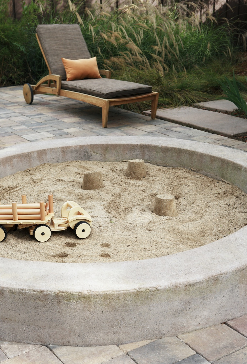 A circular concrete sandbox is fun for kids and aesthetically appealing for the adults.