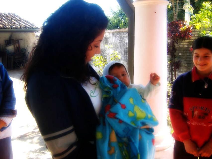 Melisa embracing a Child