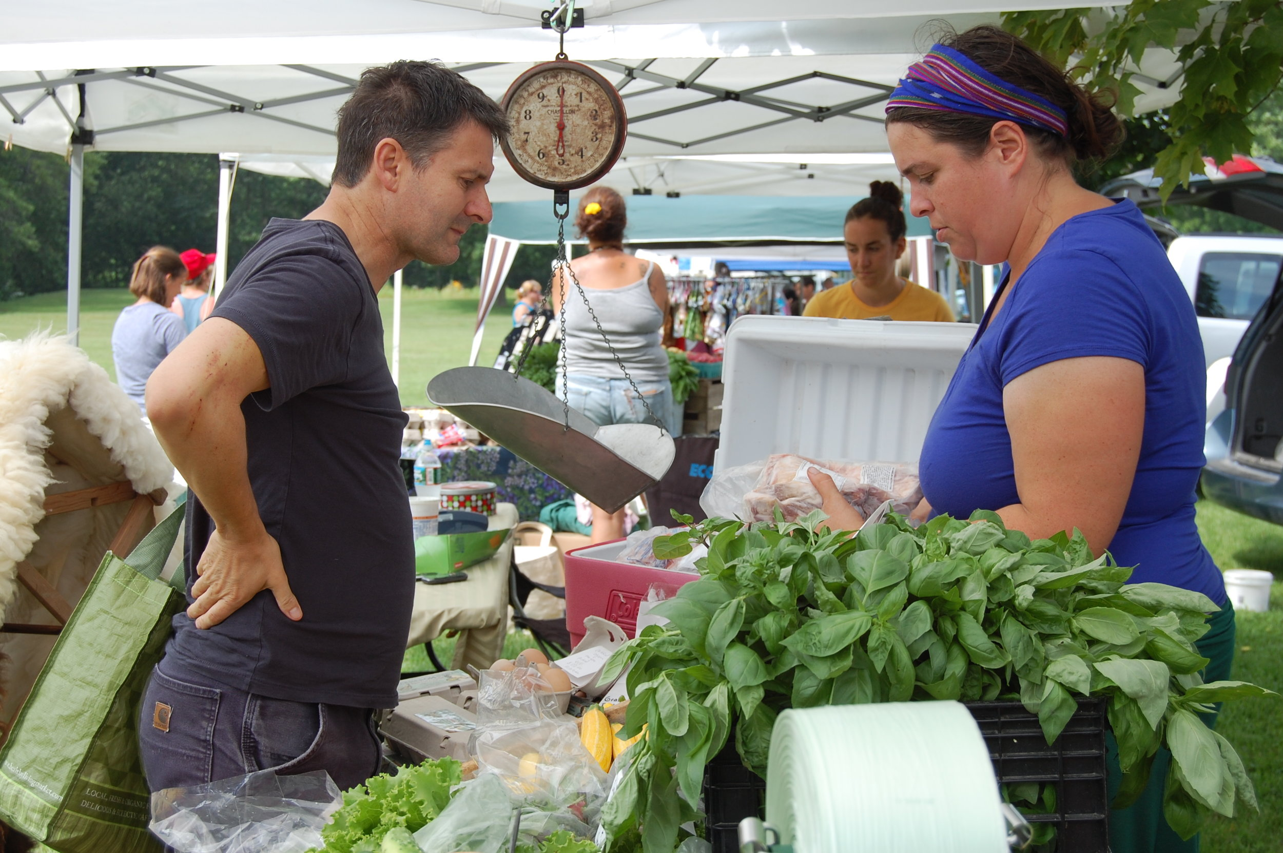 Farmer Christine Bourque shows offerings to a customer at the Champlain Islands Farmers' Market