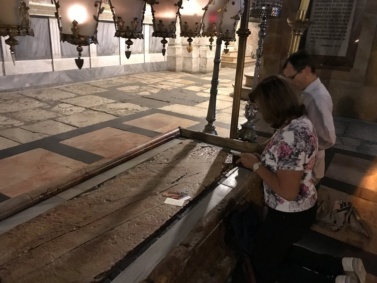 Pilgrims praying before the slab of anointing, where the Body of the Lord was anointed before burial.