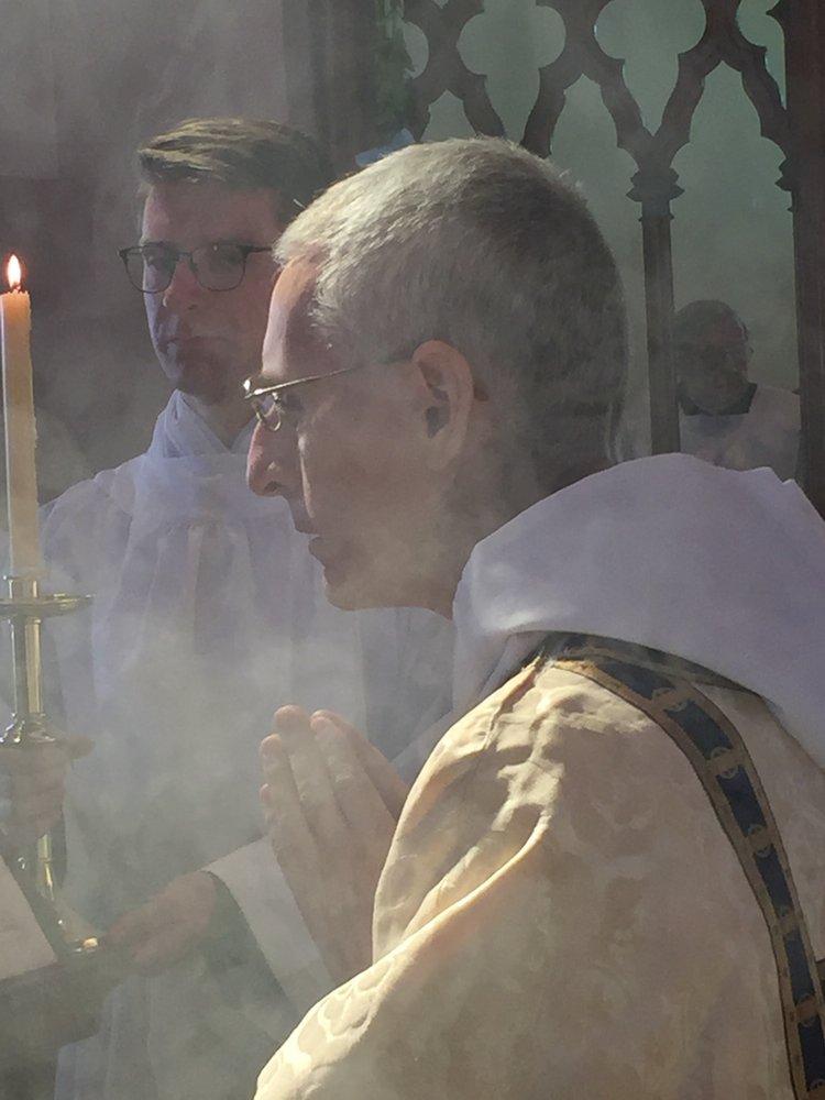 Fr Terence Naughtin chants the Gospel.