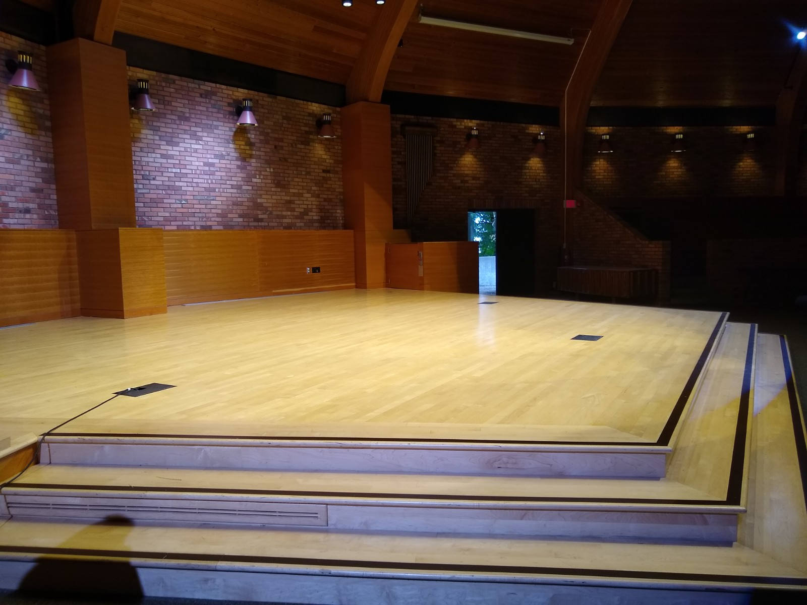 Stage, without decorative flats or curtains across back. (there will be lights and monitors along the edge of the stage, but plenty of space between them. )