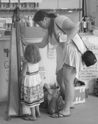Showing a child the harp and encouraging her to try to play some of the strings at the Chisago County Fair in July 2016.