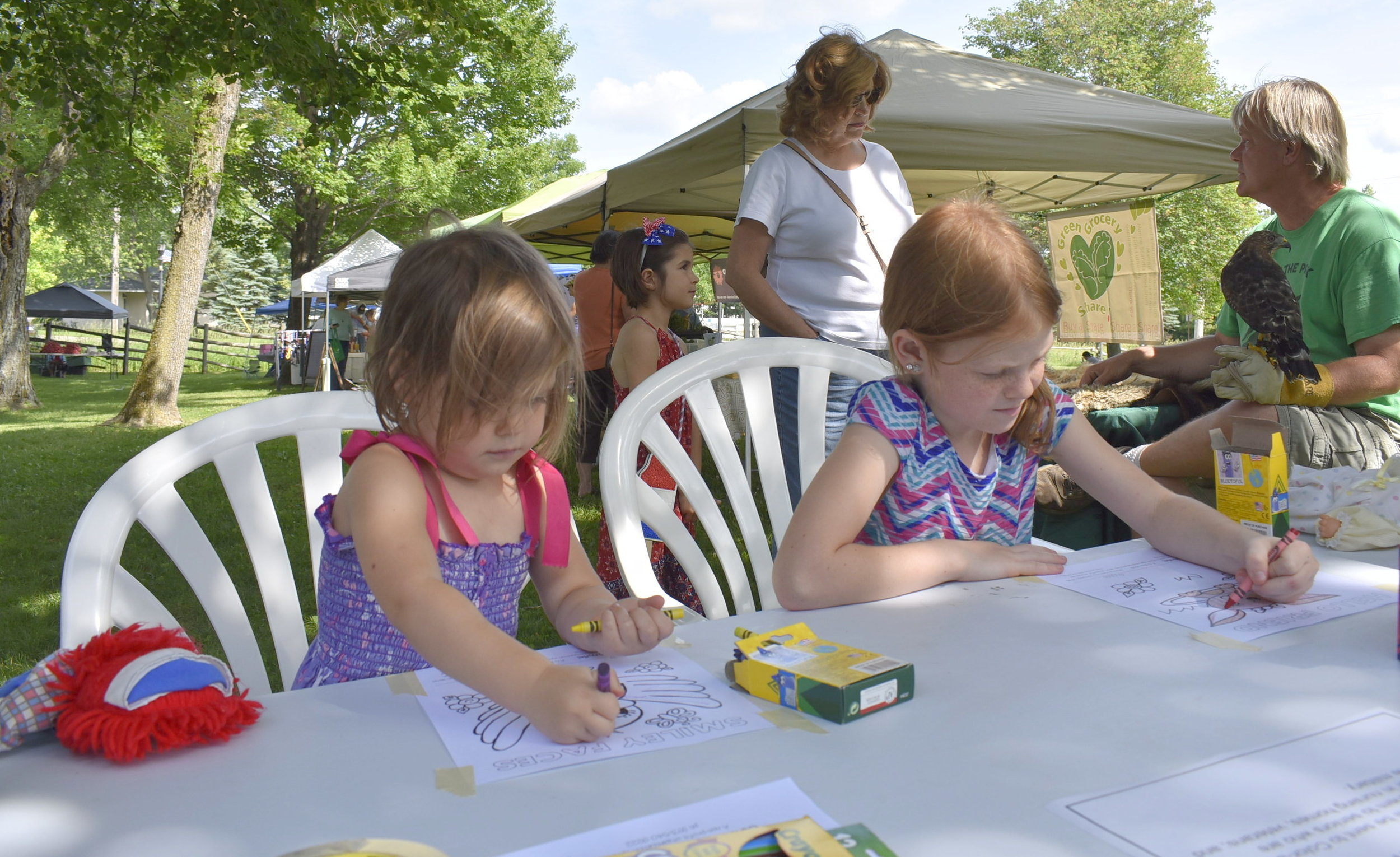 Two girls coloring photos for Color-a-Smile. The pictures will be sent to seniors in nursing homes, the homebound, veterans, and active servicemen/women throughout the U.S. and world.
