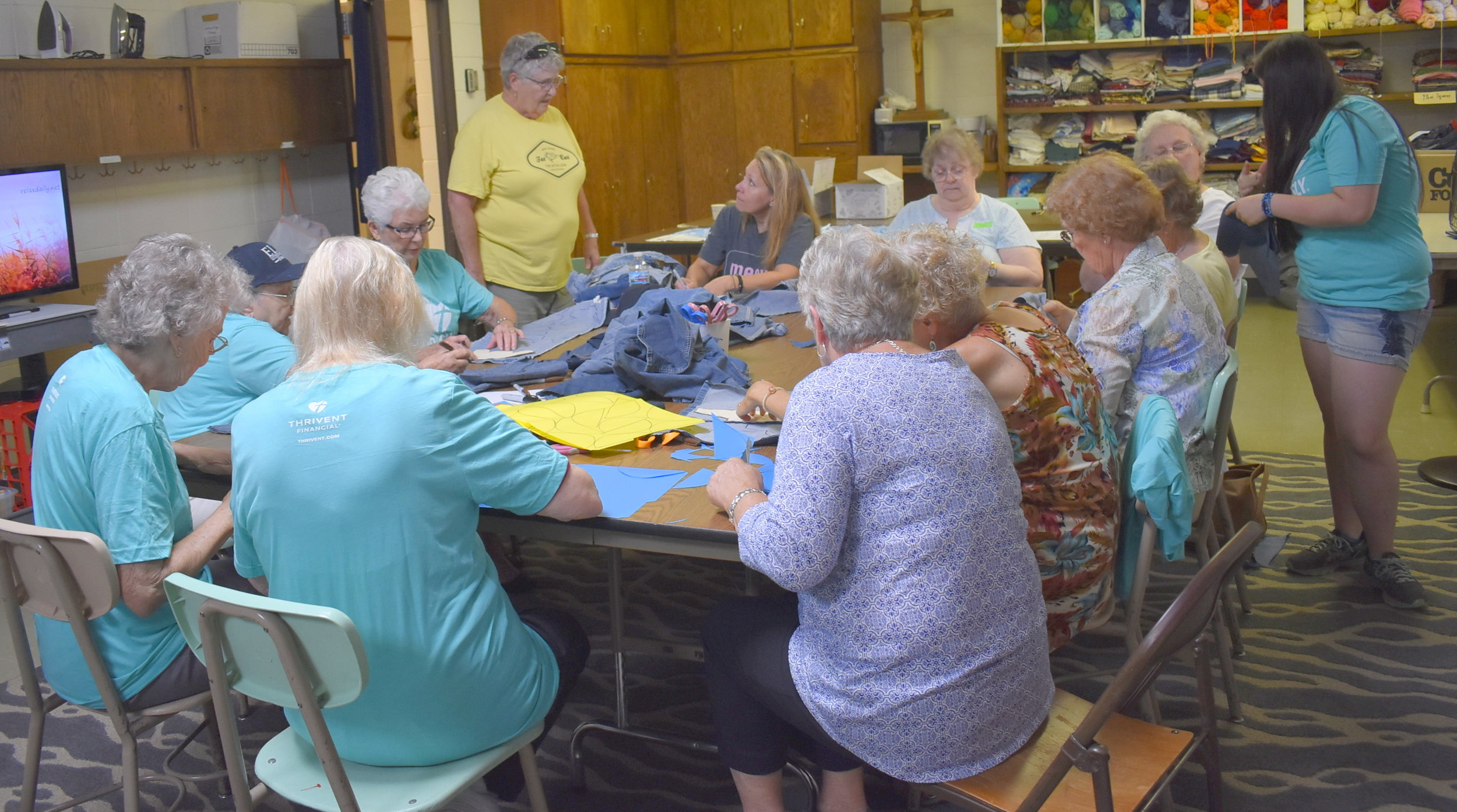 Teaching a group of women at Elim Lutheran Church how to create the parts for children's shoes from jeans and file folders. These components will be transformed by seamstresses and cobblers in Uganda into size 5 children's shoes.