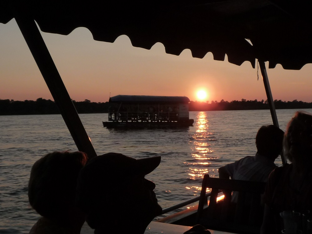 Sunset over Zambezi river with boat in background.JPG