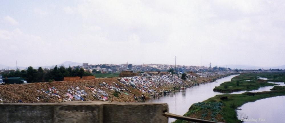 Washing day - drying washing on banks of a river in Antananarivo