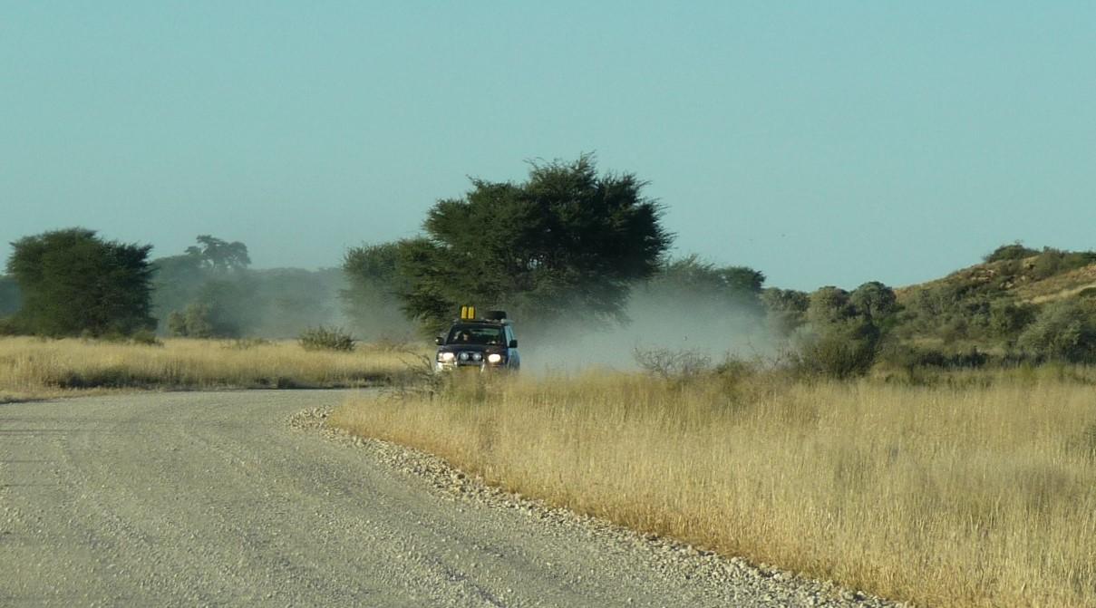 A vehicle leaving behind a trail of Kalahari dust