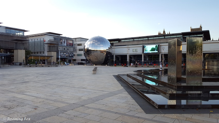 Millennium Square with its water sculpture, mirror globe and solar tree