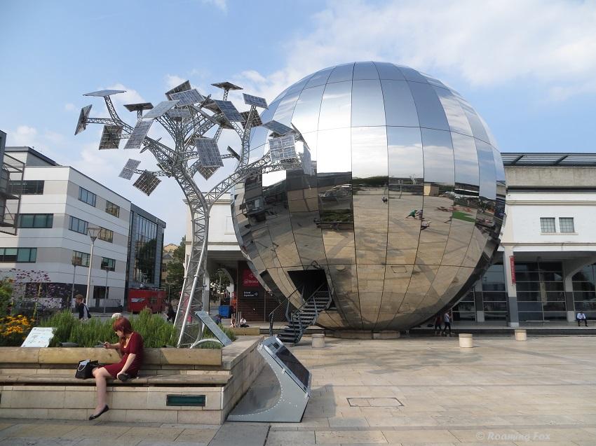 A mirror globe next to the solar tree