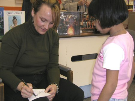 Nancy signing a book at a school visit