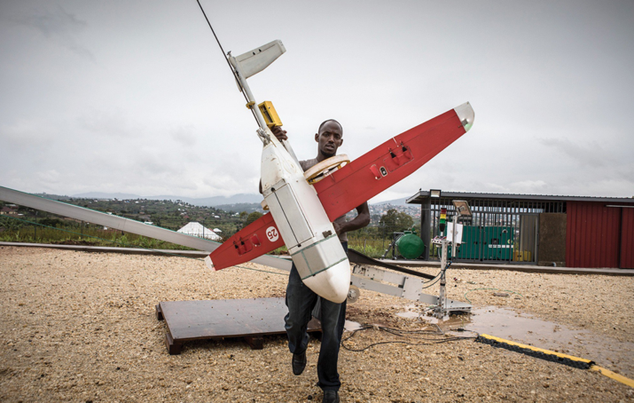 A Zipline technician carries one of the company's drones.  (Photo by MIT Technology Review)