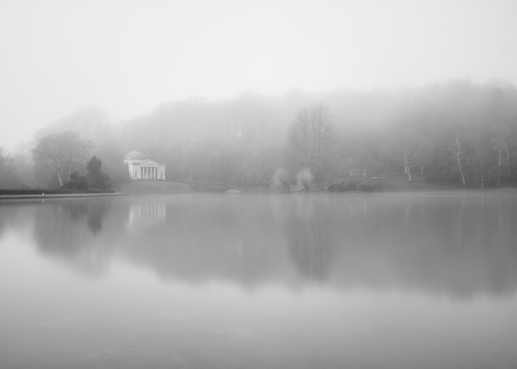 An early morning mist makes its way across the lake at Stourhead Gardens