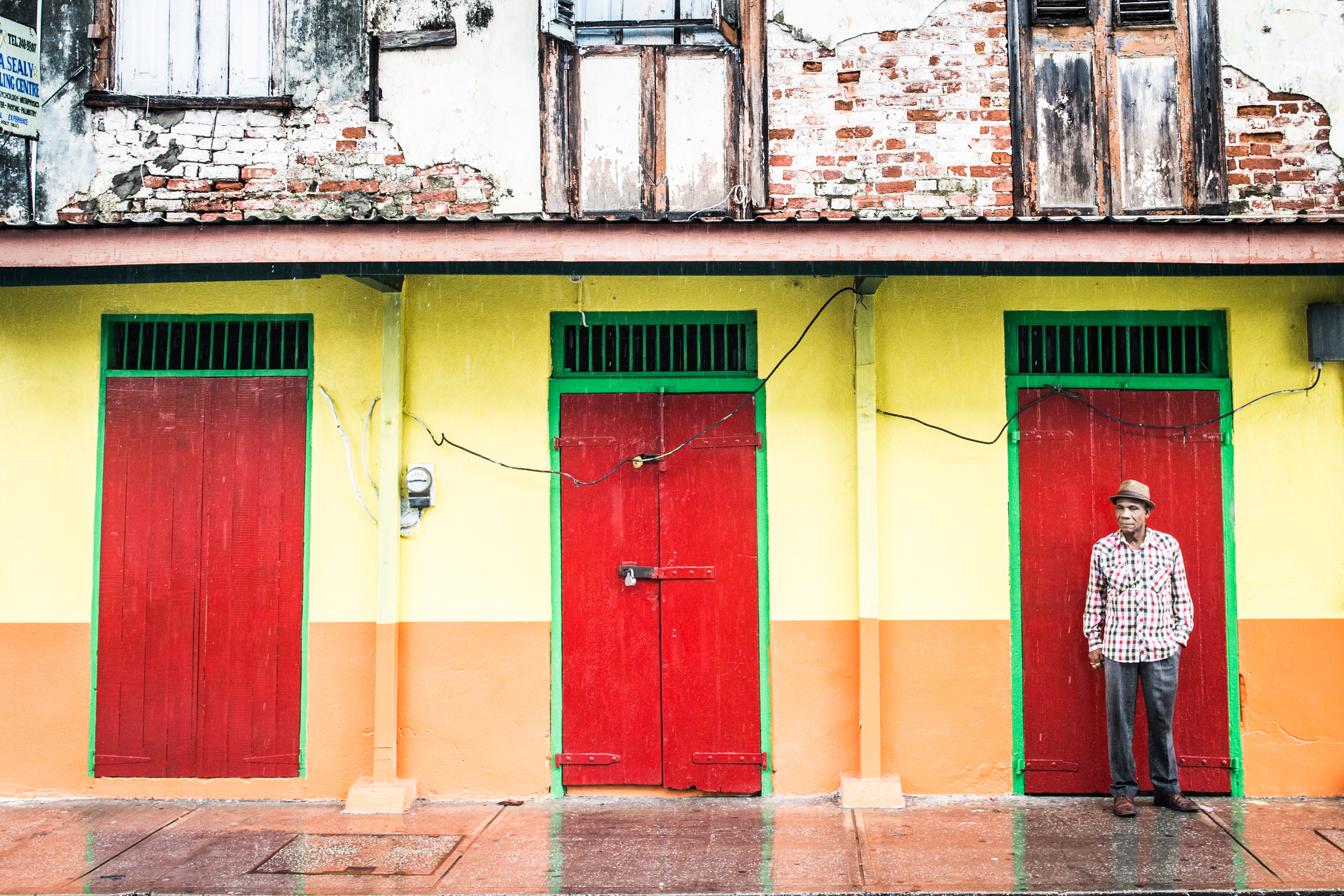 Man against colorful doors in Barbados - Travel - photo credit Nicola Bailey.jpg